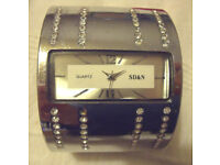 Heavy silver coloured metal women's bangle quartz analogue watch marked S D & N. £5 ovno