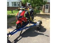 Man and a motorbike / motorcycle / scooter trailer transport