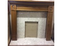 Wooden fireplace surround with marble back and marble hearth.