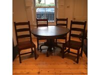 Solid wood dining table with four heavy solid chairs.