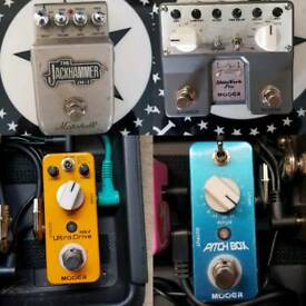 Various guitar pedals, Hercules Hangers, and a bass amp