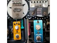 Various guitar pedals, Hercules Hangers, and a bass amp