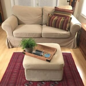 Small couch with pillows and ottoman