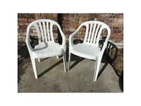 Two white plastic garden chairs