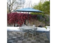 large metal garden table and chairs with parasol can deliver