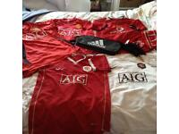 Six Manchester United shirts, two scarves and Adidas boot bag.