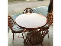 Extending wooden dining table and four matching chairs
