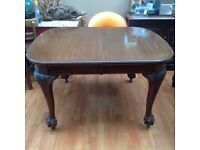 Antique dining table with lovely carving on legs and large ball and claw feet on castors