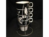TU Black & white cups in a stand . When put in order the design makes a picture. With stand