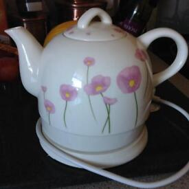 Kettle teapot with flowers on it.