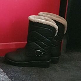 A pair of boots with fur inside.