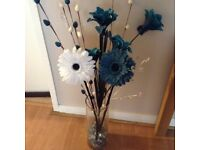 Large glass vase with faux flowers