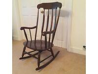 A comfortable rocking chair in dark hardwood from John Lewis