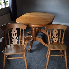 Twin pedestal pine oval extending dining table with 6 fiddleback chairs and two carver chairs.