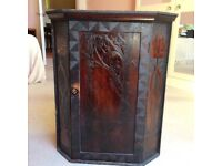 Corner cupboard with carved front