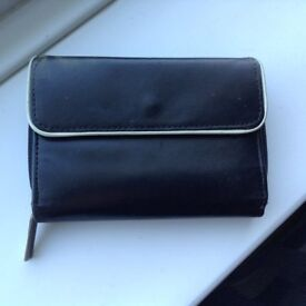 A Retro Compact Next Outer Soft Leather Black Purse with a White Rim on the Opening Cover