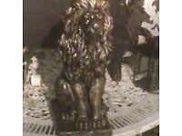Two solid concrete bronze sitting lions
