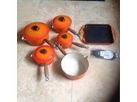 Set of orange Le Creuset saucepans