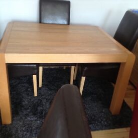 Solid oak dining table and four leather chairs in excellent condition.