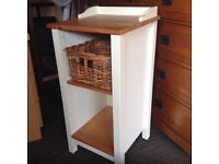 Chunky wooden bathroom floor standing storage cabinet. Pine and white with shelving and basket
