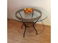 M&S round,glass top wicker table, suitable for casual dining and conservatory. Wrought iron legs.