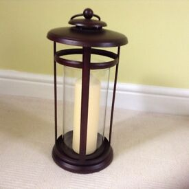 Two large glass sided lanterns with candles