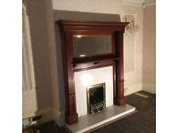 Reclaimed polished hardwood fire surround with marble hearth and back panel and fire grille.