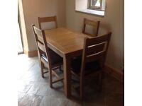 Oak dining table with four matching chairs