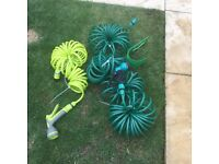 Two coiled hosepipes, 30 metre and 10 metre with tap fittings and guns