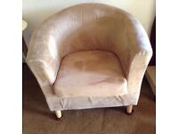 Comfortable suede tub chair in beige with removable cover on seat cushion