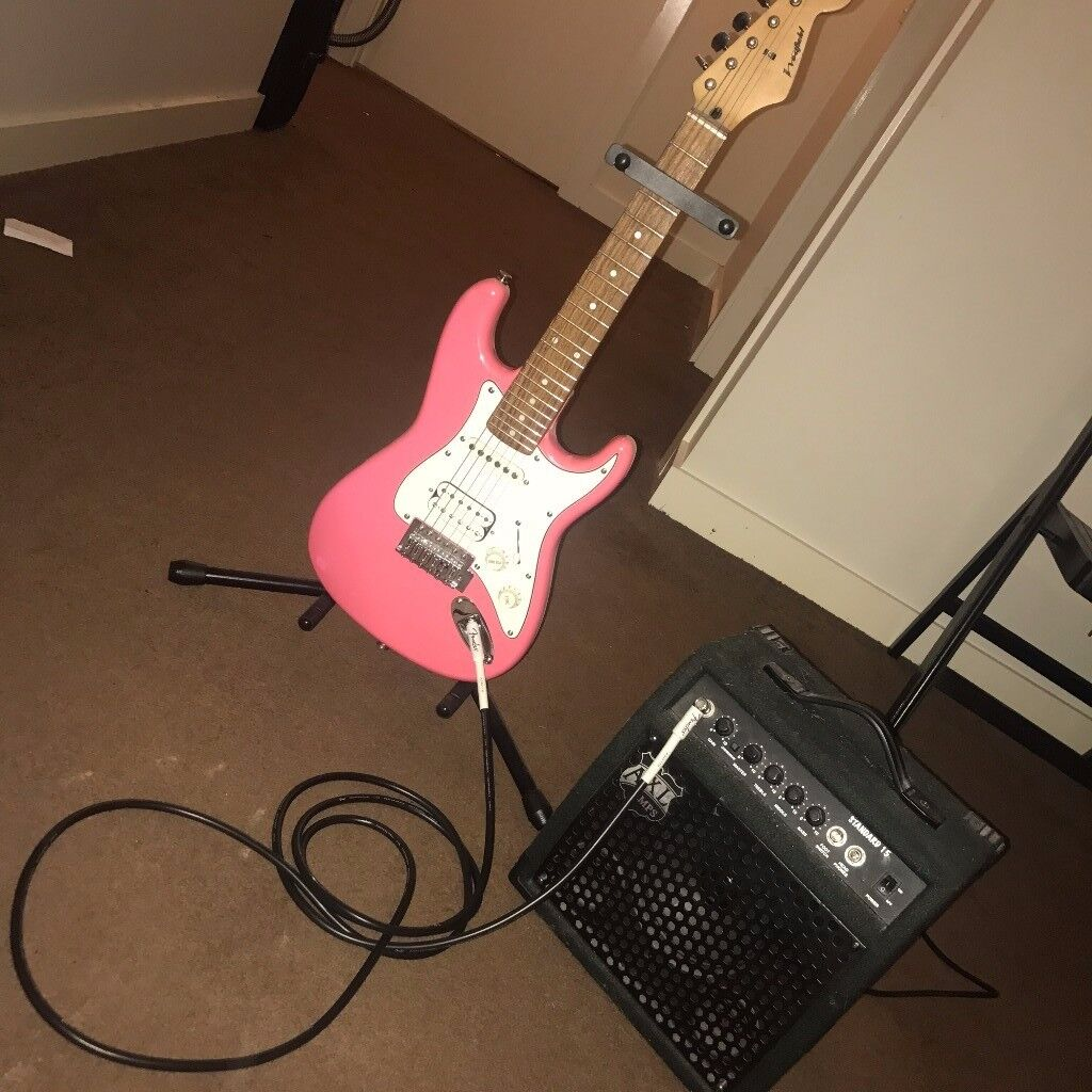 kids pink electric guitar kids amplifier and cable to connect the amp and the guitar in