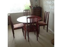 Round dining table withdrop down leaves and four dining chairs, nicely upholstered