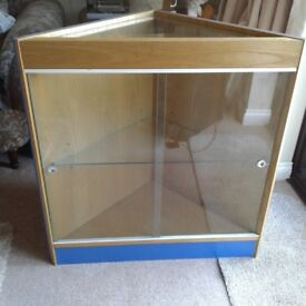 Corner display cabinet with glass top and glass front sliding doors