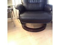Black massage chair with stool.