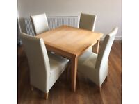 Wooden table and cream chairs
