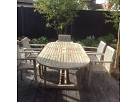 Extending teak garden table and five carver chairs