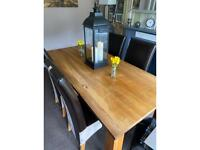 Solid oak dining table and four chairs.