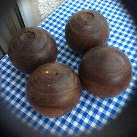 Four old wooden lawn bowls