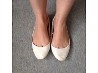 Well worn trashed white pumps
