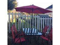 Large patio table and four red chairs and parasol