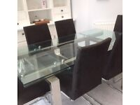 Glass/chrome dining table and six suedette black chairs
