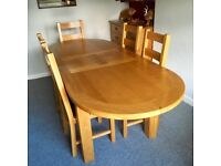 Solid oak, oval dining table and 6 oak chairs. Mint condition.