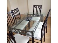 Glass table with black metal frame and 6 matching chairs.