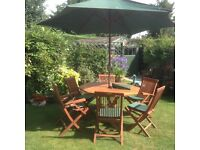 Teak table and six chairs. Also included cushions, parasol cover and base. Very good condition.