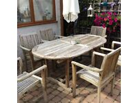 Large good quality teak garden dining table and 8 chairs with cushions