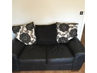Black leather sofa, fabric cushions, 2 + 3 seater and footstool
