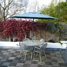 large metal garden table and 4 chairs and parasol can deliver
