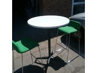 White bistro table with 2 green chairs