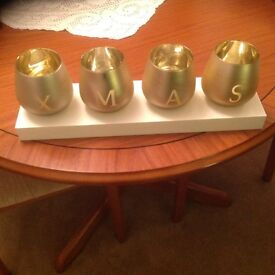 4 candle holders on plinth spells Xmas
