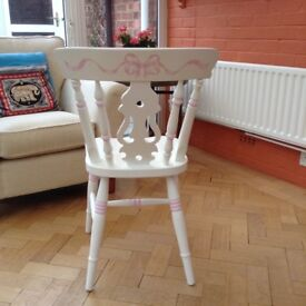 White wooden chair with pink detail, suitable for girl's room.